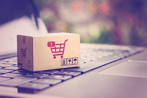 Un ordinateur et un carton avec l'icone du panier, symbole du e-commerce