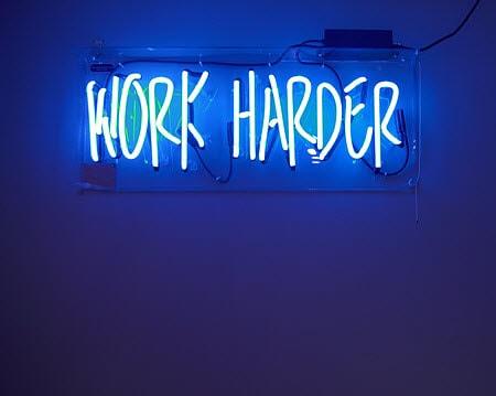 """Un panneau lumineux avec marqué """"Work Harder"""", travailler dur"""